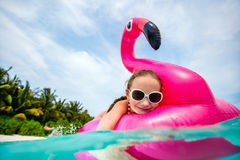 Little girl swimming. Split underwater photo of adorable little girl with pink flamingo inflatable ring swimming in a tropical ocean on summer vacation stock images