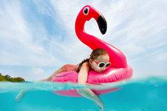 Little girl swimming. Split underwater photo of adorable little girl with pink flamingo inflatable ring swimming in a tropical ocean on summer vacation royalty free stock image