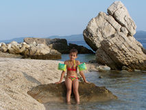 Little girl in swimming suit posing on the rocky beach. Wild croatian rocky beach with a little caucasian girl posing and sitting on the rock Royalty Free Stock Photography