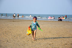 Little girl in swimming suit walk on the sand with toys Royalty Free Stock Photo