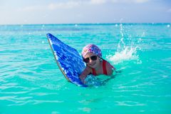 Little girl swimming on surfboard in the turquoise Royalty Free Stock Photos