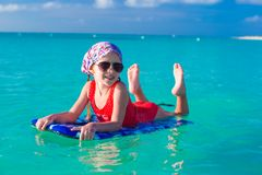 Little girl swimming on a surfboard in the turquoise sea Royalty Free Stock Photo