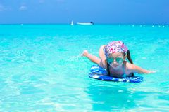 Little girl swimming on a surfboard in the turquoise sea Royalty Free Stock Photos