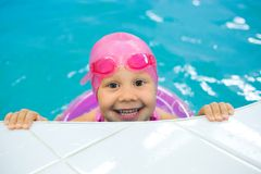 Little girl swimming  in swimming pool Royalty Free Stock Images