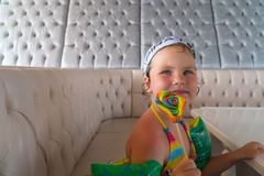 Little girl after swimming is to eat colorful Lollipop Stock Image