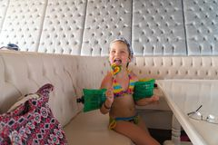 Little girl after swimming is to eat colorful Lollipop Royalty Free Stock Image
