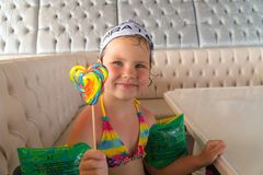 Little girl after swimming is to eat colorful Lollipop Stock Photos