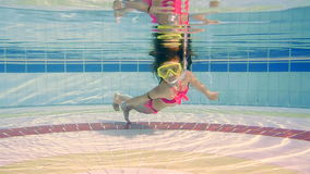 Little girl swimming under water in the pool stock footage