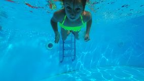 Little girl swimming under the water in swimming pool stock video footage