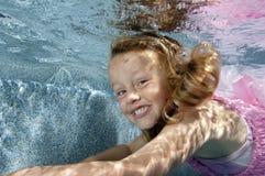 Little girl swimming underwater stock images