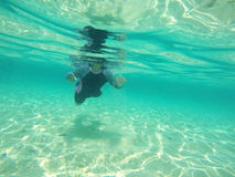 Little girl swimming underwater without equipment. Little girl swimming underwater without equipment Royalty Free Stock Photos
