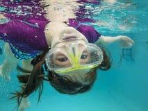 Little girl swimming underwater having fun. Little girl having fun and swimming upside down underwater Stock Photos