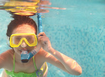 The little girl swimming underwater and smiling Stock Image