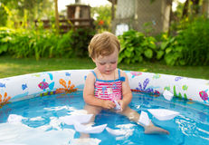 The little girl swims in a paddling pool. Royalty Free Stock Images
