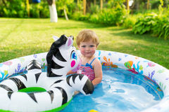 The little girl swims in a paddling pool. Stock Image