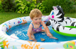 The little girl swims in a paddling pool. Stock Photo