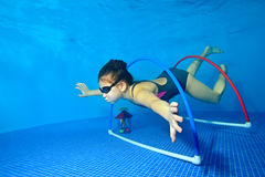 Little girl swims and plays sports underwater in the pool on a blue background, and floats through the hoops at the bottom. Shooting under water. Portrait Royalty Free Stock Photo