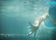 Little girl swims in the pool underwater. Little girl in a bathing suit swims in the pool underwater Stock Images