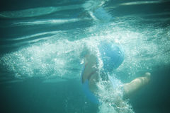 Little girl swims in the pool underwater Royalty Free Stock Images