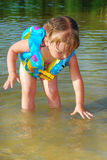 A little girl swims in the river. Royalty Free Stock Photography