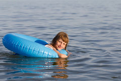Little girl swims in a sea in an blue life preserv Stock Photography