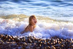 The little girl swims in the sea. Laughs, the wave has covered Royalty Free Stock Image