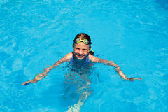 Little girl swims in swimming pool. Happy little girl swims in swimming pool Royalty Free Stock Images