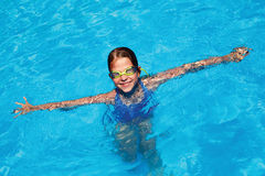 Little girl swims in swimming pool. Happy little girl swims in swimming pool Stock Images