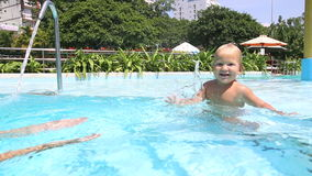 Little girl swims underwater by herself to mother in pool stock video footage
