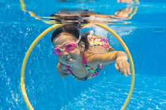 Little girl swims underwater. Kid in pool Stock Photos