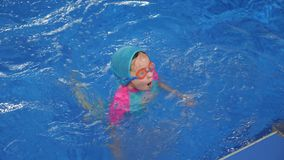 Little girl in swimsuit, cap and goggles is diving and swimming to egge of pool. Cute little girl is lerning to swim in swimming pool in slow motion. She is in stock footage