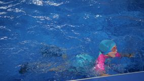 Little girl in swimsuit, cap and goggles is diving and swimming to egge of pool. Cute little girl is lerning to swim in swimming pool in slow motion. She is in stock video