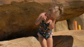 Little girl fool around in the pool. Little girl in a swimsuit fool around in standing on the stones in the pool stock footage