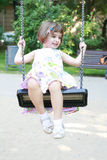 Little girl on the swing. In the playpen having fun stock photos