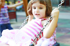 Little girl on the swing. In the playpen having fun stock images