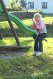 Little girl on a swing. Little girl swinging on a rope swing royalty free stock photos