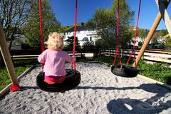 Little girl on swing. A view of a little toddler as she sits on a swing in a backyard or neighborhood playground royalty free stock photos