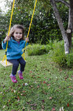 Little girl on a swing. In the garden at home stock photo