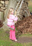 Little girl on a swing. Little girl in pink clothes sitting on a swing with autumn leaves, tree and stones behind Royalty Free Stock Images