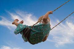 Little Girl on Swing. Pretty little blond girl on a swing against a beautiful blue sky background stock photos