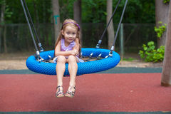 Little girl on swing at an amusement park Royalty Free Stock Images
