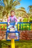 Little girl on swing in children's city park Stock Photography