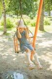 Little girl on swing in children's city park Royalty Free Stock Image