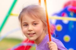 Little girl on the swing. Closeup portrait of a cute little girl on the swing on playground, happy child with pleasure spending time in the yard, enjoying spring stock image