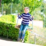 Little girl on swing. Happy little girl on swing in park Stock Image