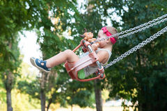 Little girl on swing. With headband and plush teddy bear royalty free stock images