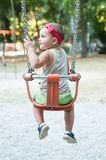 Little girl on swing. With headband at the public park stock images