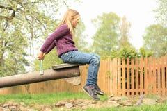 Little girl on a swing. Little heary girl in violet pullower swinging on a wooden swing Stock Photo