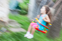 Little girl on swing with motion blure. Blurred photo stock photography
