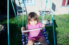 Little girl on swing outdoor at summer. Child playing activity royalty free stock images